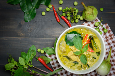 scrumptious: green curry with chicken (Kang Keaw Wan Gai) with brown tablecloth and vegetable on wooden background top view, Thai local food