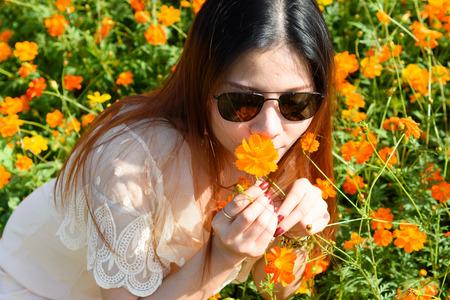 closeup portrait of woman wear a sunglass kissing an orange flowers