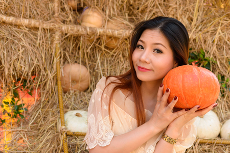 closeup portrait of happy woman and holding a big orange pumpkin in hand Stock Photo