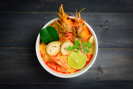 Tom Yum Soup or River Prawn Spicy Sour Soup (Tom Yum Goong) on wooden table top view, Thai local food