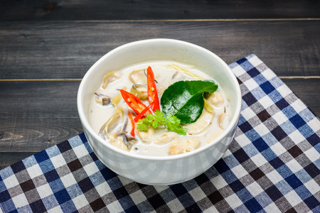coconut milk soup with chicken or Thai chicken coconut Soup ( Tom Kha Gai ) on wooden with table cloth, table top view, Thai local food