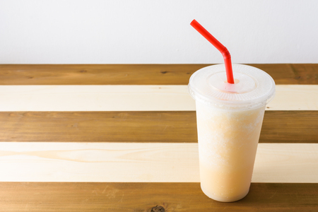 smoothies of fruit juice on wooden background with red tube