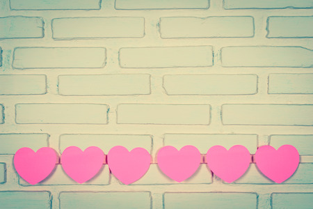 Pink sticky notes hearts shaped hearts lined holes on the wall. vintage style Stock Photo
