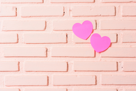 Pink sticky notes hearts shaped lined holes on the wall Stock Photo