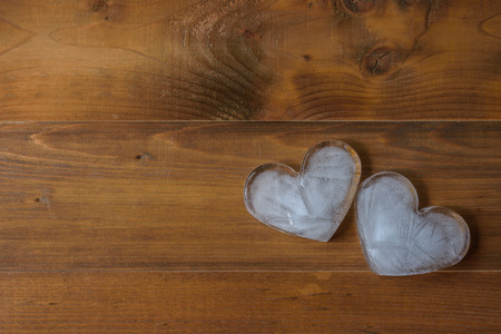 Heart-shaped ice on brown wooden background