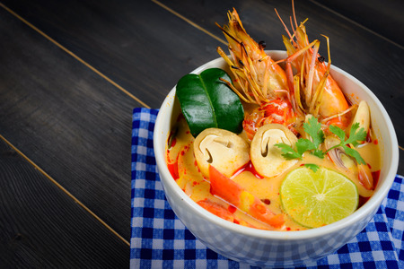 Closeup Tom Yum Soup or River Prawn Spicy Sour Soup (Tom Yum Goong) on wooden table with blue tablecloth, Thai local food