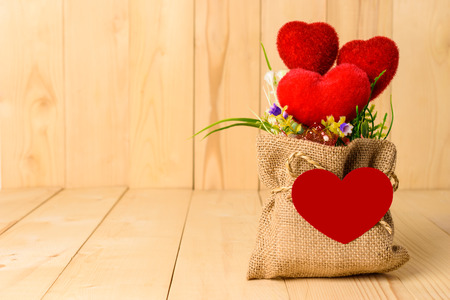 plastic bouquet and hearts in sack with a blank red paper are heart shapes on wooden background