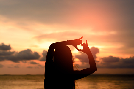 woman hands forming a heart with sunset silhouette Stock Photo