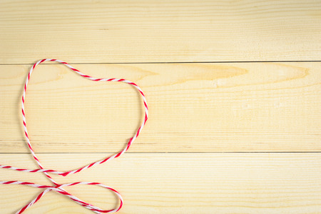 rope shaped red heart on wooden background or backdrop Stock Photo