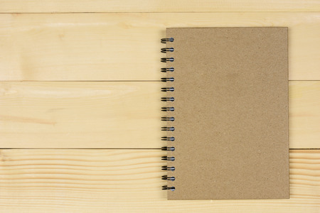 Brown notebook made from recycled on wooden background with copy space