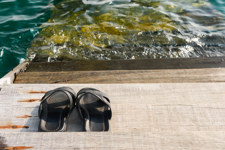 pair of black mens sandals flip flop on a plank at waterfront