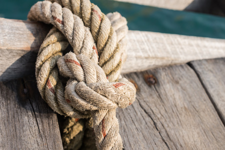 Rope tied up to a knot on a wood bridge