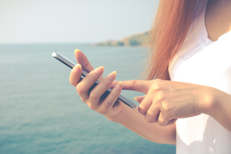Close up of women wear a white shirt holding cell telephone and sea background Stock Photo