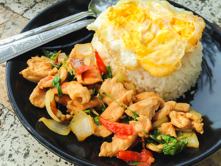 Rice topped with stir-fried chicken and basil fried egg, Thai local food