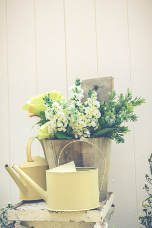 decorate watering can and plastic flower in the wooden buckets in white plank background retro style