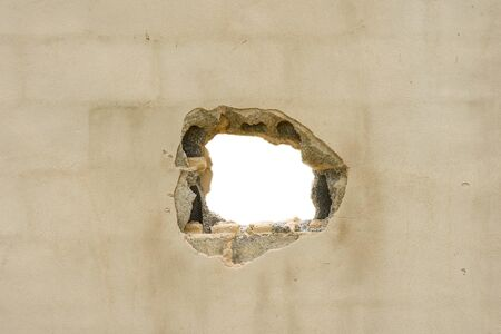 Hole in the concreate wall with white background