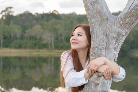Portrait asian woman feelling freshness and hug the tree in the forest