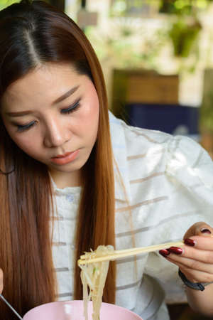 Young asian woman eating noodle soup