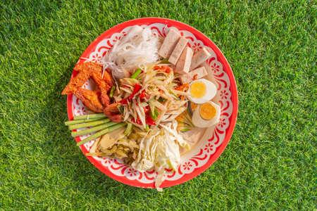 Papaya salad (som tum) tray spicy on green grass, Thai local food top view, close up.