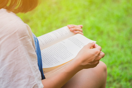 release: The woman reading book on the lawn. release concept. Stock Photo