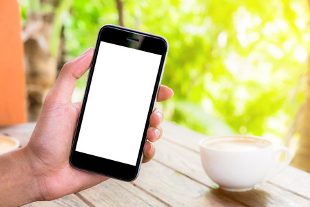 hand holding smart phone showing white screen with laptop and earphone on the desk. Smartphone with blank screen and can be add your texts or others on screen. Stock Photo