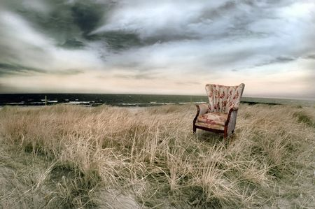 Stormy beach with wingback chair in infrared.