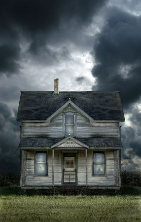 Old haunted farmhouse under a stormy sky. Stock Photo