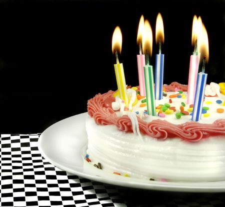 Birthday cake with lit candles on black background. Stock Photo