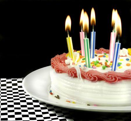 Verjaardagstaart met aangestoken kaarsen op zwarte achtergrond. Stockfoto