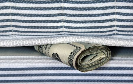 A roll of money tucked in a mattress for safekeeping. photo