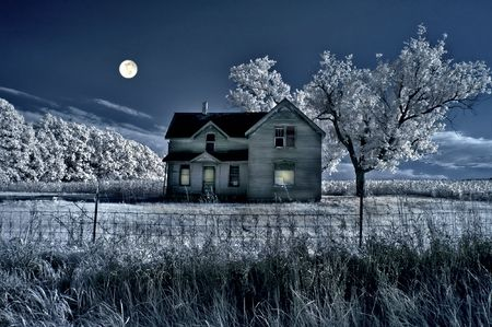 Haunted farmhouse under a full moon in infrared.