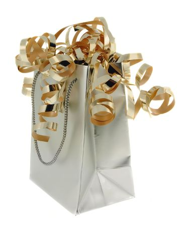 Silver gift bag with gold ribbons against a white background. Stock Photo