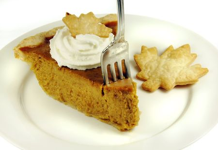 Fork in a pumpkin pie slice with whipped cream. photo