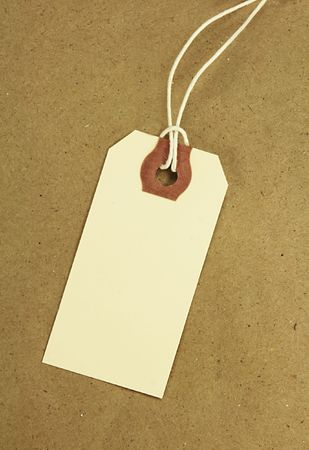 Blank tag with string on brown paper. Stock Photo
