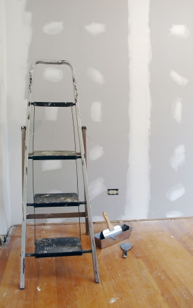 construction project: New sheetrock and ladder for home improvement. Stock Photo