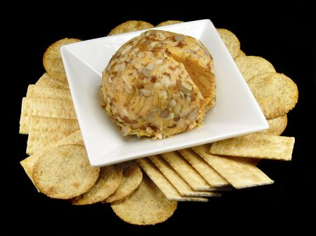 Cheese ball and crackers with a black background.