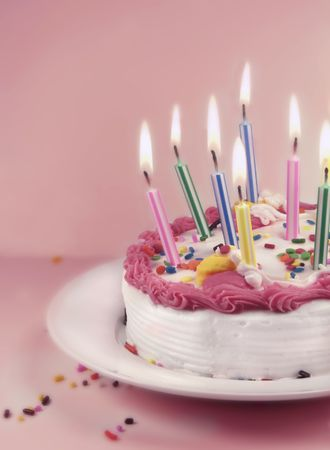 Birthday cake and candles on a pink background. Stock Photo