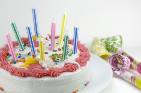 blowers: Birthday cake and party blowers on a white background.