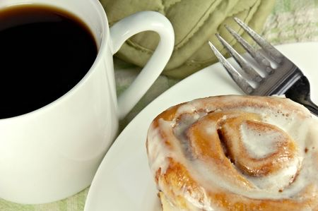 Cinnamon Roll with coffee and a fork.