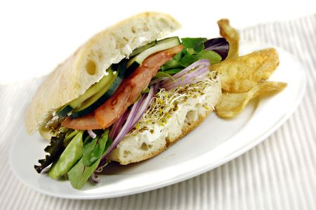 Healthy veggie sandwich with cucumbers, tomatoes, lettuce, onions and sprouts. photo