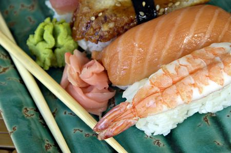 Different types of sushi with chopsticks on an Asian plate. Imagens