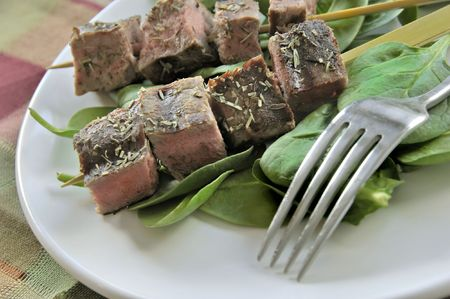 cubed: Cubed and skewered steak on a bed of spinache leaves.