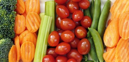 Raw vegetables to eat with dip including carrots, sugar snap peas, tomatoes, broccoli, and celery sticks. Stock Photo