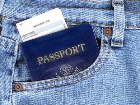 Passport and boarding pass sticking out of blue jeans pocket. Stock Photo