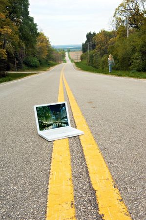 going nowhere: Laptop Computer sitting in the middle of a country road. My photograph is on the screen. Woman is walking away.
