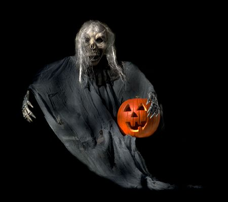 malevolent: Frightening Halloween ghoul with a jackolantern in his arm. Stock Photo