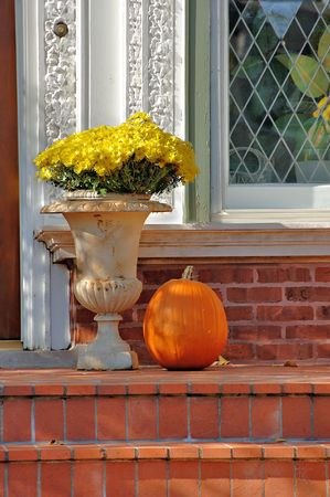 stoop: Brick porch with yellow chrysanthemums and a pumpkin in the autumn. Stock Photo