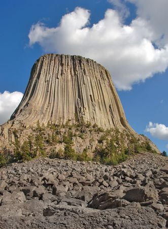 geological formation: Devils Tower National Monument in Wyoming with white fluffy clouds.