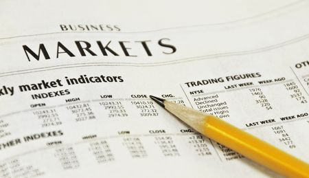Market Report in the newspaper with a yellow pencil.