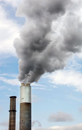 Smokestack of an electrical power plant billowing smoke. Stock Photo
